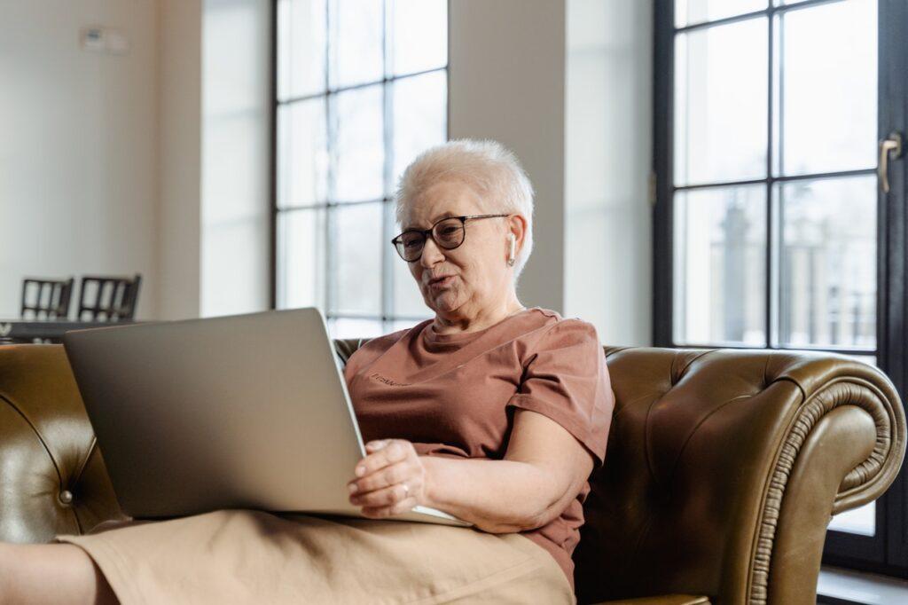 Seniorka z laptopem na sofie