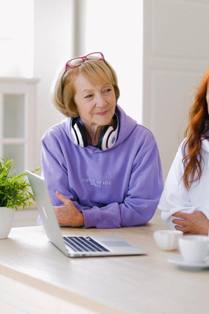 Seniorka ze słuchawkami i z laptopem
